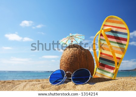 Still life on the beach with sunglasses cocktail in coconut and flip flop - stock photo