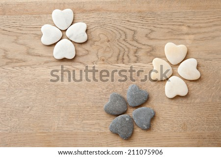 Still life over head close up view of multiple heart shaped natural stones laying on a wooden texture table in a floral formation. Health spa interior view of nature elements and relaxing treatments. - stock photo