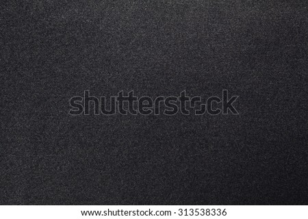 Still life paper texture background with a grain noise effect, full frame. Close up detail of textured sheet of paper blank page with dark gray dye on organic art paper. Background wall black color. - stock photo