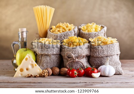 Still life - pasta and seasoning ingredients on old table - stock photo