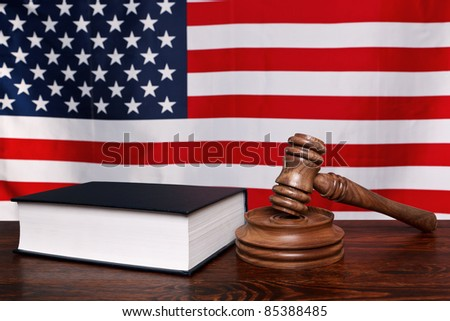 Still life photo of a gavel, block and law book on a judges bench with the American flag behind. - stock photo