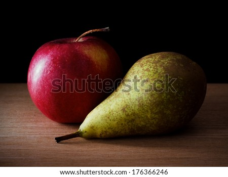 Still life photo of red apple and pear on table - stock photo
