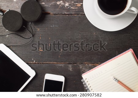 Still life photo of Smartphone, Tablet, Notebook, Headphone, Coffee on Old Wooden table background - stock photo