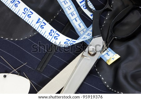 Still life photo of the inside of a bespoke suit jacket with hand stitching and scissors, tape measure, chalk and pins. - stock photo