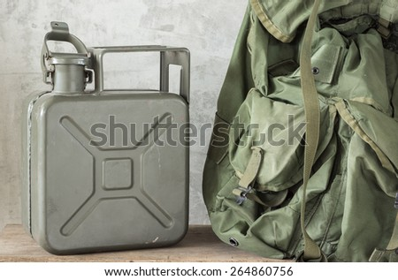 still life photography : Army green jerrycan ( fuel canister ) with part of Military backpack on old wood - stock photo