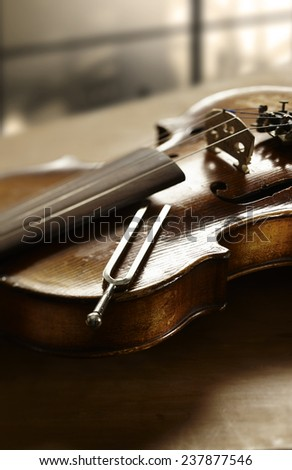 Still life photography of violin and tuning fork - stock photo