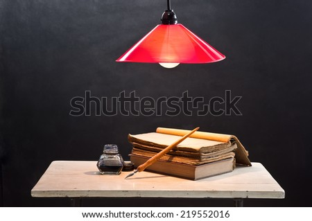 still life photography, opening old book on old table with quill pen inkwell and lighted lamp - stock photo