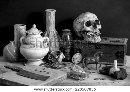 still life photography, skull with dry rose in the mouth and wooden box, candle, chopping block, clock, metal horse, egg, old knife, lamp, nest, pottery, rosary and wicker in black and white - stock photo