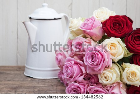 still life picture of a rose bouquet and an old coffee can