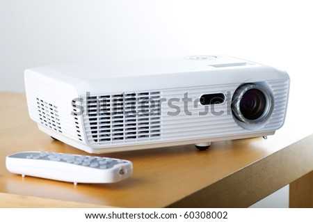 Still life picture of projector and remote control on the table - stock photo