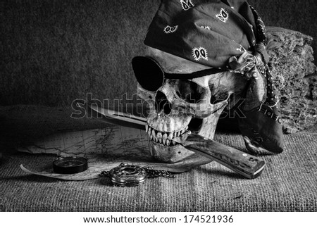 Still life, pirate skull with knife in the mouth, compass on floor and pocket watch on the floor