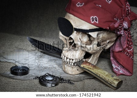 Still life, pirate skull with knife in the mouth, compass on floor and pocket watch on the floor - stock photo