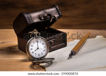 Still life, pocket watch with small leather box and dip pen on burn paper - stock photo