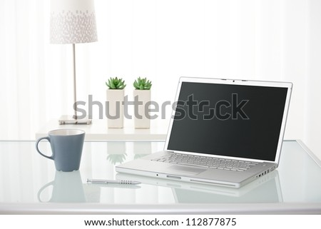 Still-life portrait of computer, pen, coffee mug on table, lamp and plants in bright environment.
