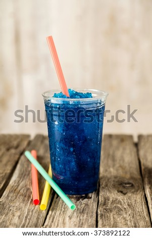 Still Life Profile of Refreshing and Cool Frozen Blue Fruit Slush Drink in Plastic Cup Served on Rustic Wooden Table with Collection of Colorful Straws - stock photo