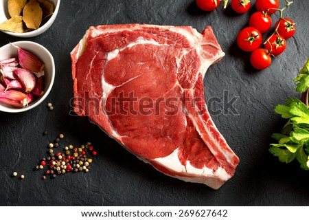 Still life raw thick rib over black background from above - stock photo