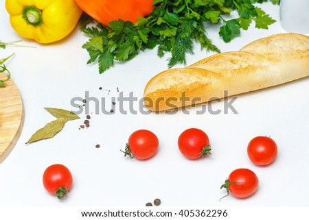 Still life. Ripe vegetables, bread and tomatoes at the kitchen table. Dinner time. - stock photo
