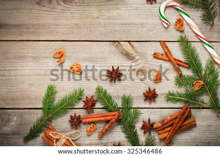 Still life, seasonal and holidays concept. Christmas decoration with fir tree, sugar cane and spices (cinnamon, anise star) on a wooden table. Selective focus, copy space, top view