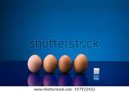 Still life showing amount of sugar in four eggs - stock photo