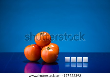 Still life showing amount of sugar in four tomatoes - stock photo