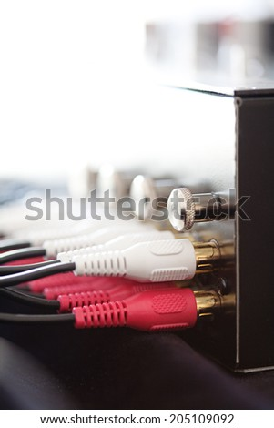 Still life side view of a musical electronic device with multiple pluggings jacks inputs in red and white, against a bright light in an audio recording studio interior. Technology and equipment. - stock photo