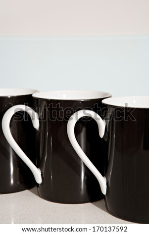 Still life side view of three black and white tea mugs aligned together on a kitchen counter. Home interior coffee drinking detail. - stock photo