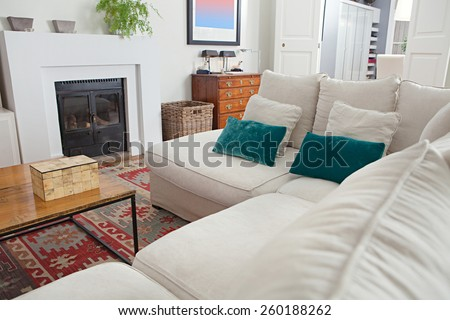 Still life view of a stylish, elegant home living room with a white sofa and a fireplace, wooden floors and carpets, house interior. Beautiful home space family room with books and cushions, indoors. - stock photo