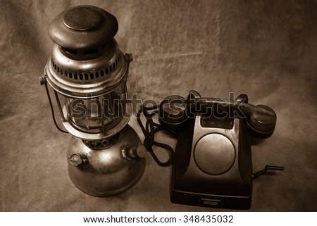 Still life Vintage black phone, Old hurricane lamp sepia tone - stock photo