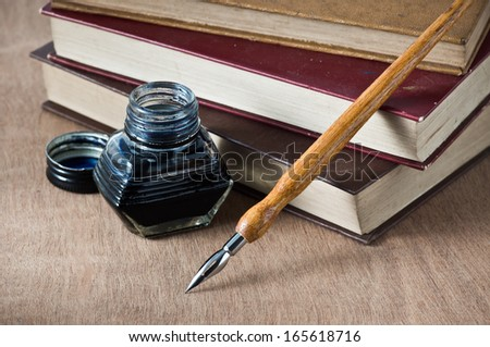 still life, vintage books are stacked on wooden table with quill pen and inkwell - stock photo