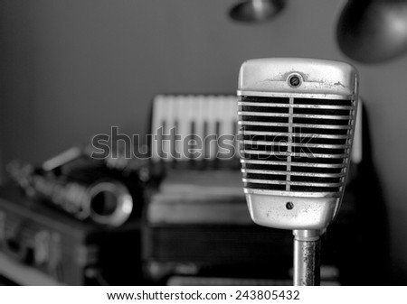 Still life vintage music concept selective focus on microphone with saxophones and accordion background black and white version - stock photo