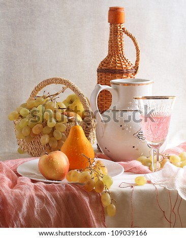Still-life, wattled basket with juicy fruit and a jug - stock photo