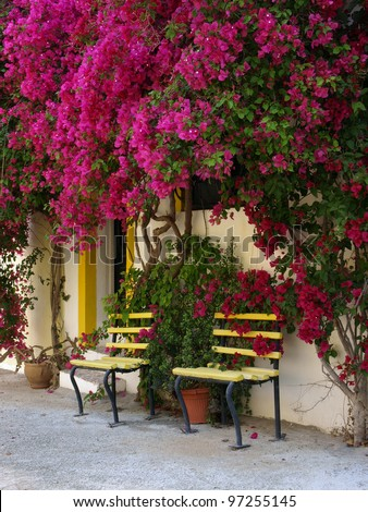 Still life whit flowers and bench over Spanish house - stock photo