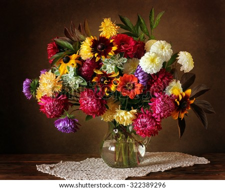 Still life with a beautiful bouquet of cultivated flowers in a glass jug on a dark brown background. Autumn flowers, bouquet as a gift. It is possible to use as a congratulation. - stock photo