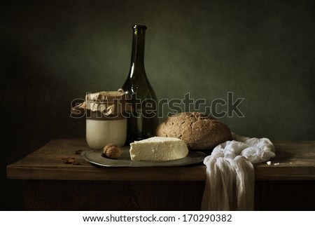 Still life with a bottle of wine and fresh bread - stock photo
