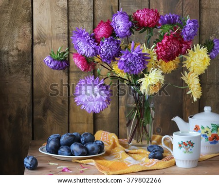 Still life with a bouquet of asters, plums, a Cup and the teapot. - stock photo