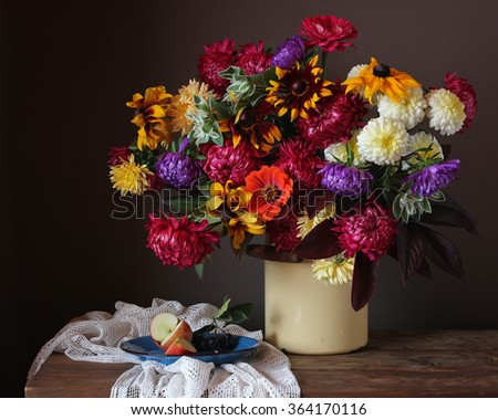 Still life with a bouquet of autumn flowers in a can and apple slices on a blue plate. - stock photo