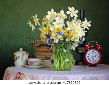 Still life with a bouquet of daffodils in glass jug, books, alarm clock and old utensils on the table with a white tablecloth with lace on green background. - stock photo