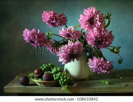 Still life with a bouquet of dahlias and plums - stock photo