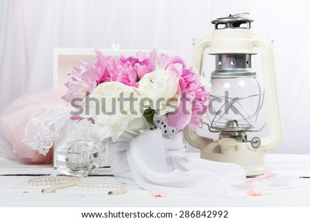 Still-life with a bouquet of peonies and old kerosene lamp