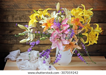 Still life with a bouquet of yellow and pink lilies against from boards - stock photo