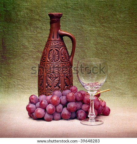 Still-life with a clay large bottle, a glass and grapes against a canvas - stock photo
