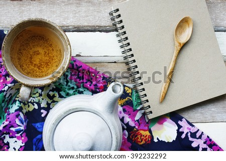 still life with a cup of tea with teapot  and note book on wooden table.flat lay - stock photo