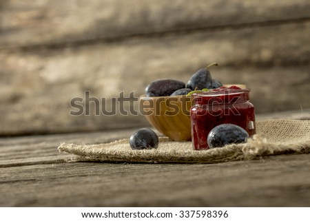 Still life with a jar of home made plum marmalade and wooden bowl full of fresh juicy plums on a burlap cloth lying on a textured rustic wooden desk. - stock photo