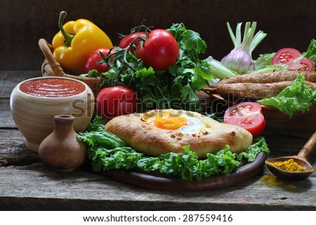 Still-life with a pie and ljulja-kebab submitted with fresh vegetables and tomato sauce  - stock photo
