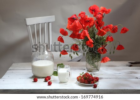 Still-life with a strawberry and poppies, a magnificent bouquet from bright red poppies and a juicy ripe sweet appetizing strawberry and fresh rural milk in a transparent glass mug - stock photo