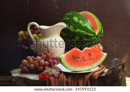 Still-life with a water-melon, grapes, a guelder-rose and a white jug - stock photo
