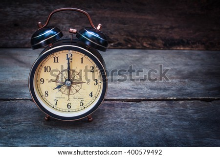 Still life with alarm clock on wood table ( alarm clock show 8 o`clock ). - stock photo