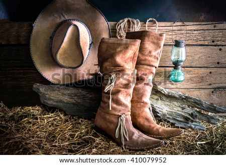 Still life with american west rodeo brown felt cowboy hat and traditional leather boots in vintage ranch barn background - stock photo
