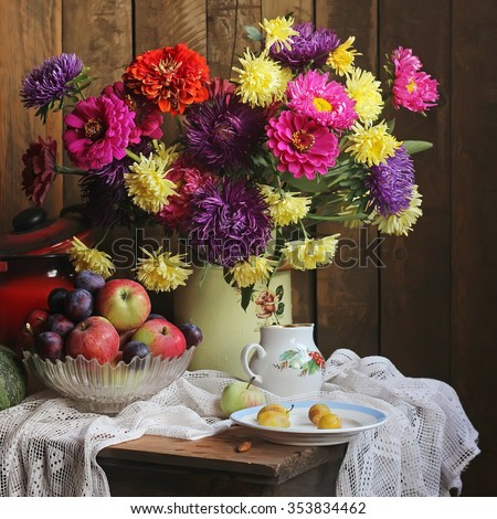 Still life with an autumn bouquet, apples and plums against from boards. - stock photo