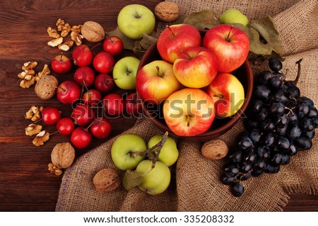 Still Life with Apples different sorts and calibers, blue grapes and walnuts on a wooden background. The concept of harvest